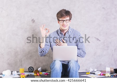 Smiling caucasian male with laptop sitting on messy desktop and showing ok sign - stock photo