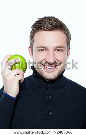 Smiling caucasian man holding an apple looking at the camera - stock photo