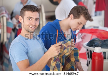 Smiling Caucasian man holds plaid shirt in laundromat - stock photo