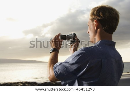 Smiling Caucasian man photographing a scenic sunset at a beach. Horizontal format. - stock photo
