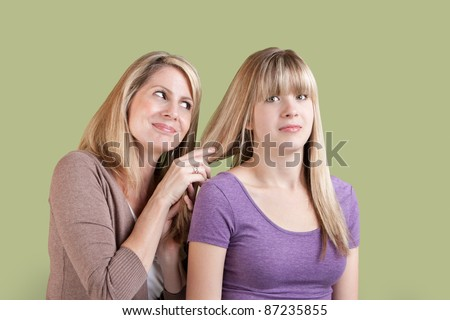 Smiling Caucasian mom with annoyed daughter over green background - stock photo