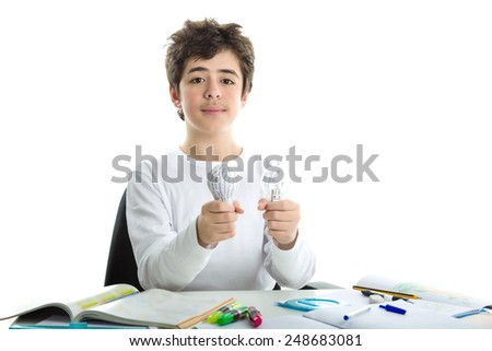 Smiling Caucasian smooth-skinned boy wearing a white long sleeve t-shirt is holding a real glass lightbulb and a 3D print prototype while sitting in front of his homework - stock photo
