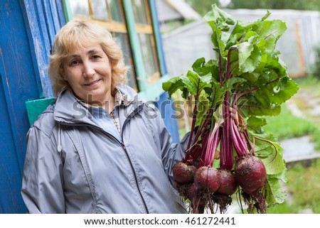 Smiling Caucasian woman holding fresh beet in hand while standing on porch of house