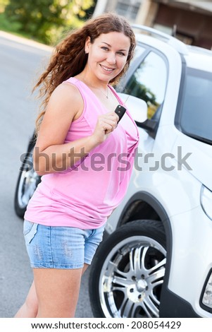 Smiling Caucasian woman holding ignition key in hand - stock photo