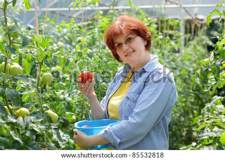 Smiling caucasian woman holding tomato in  hand