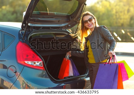 Smiling Caucasian woman putting her shopping bags into the car trunk
