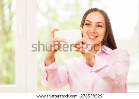 Smiling caucasian woman with pink shirt is doing a selfie with her phone - stock photo