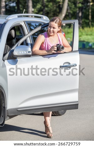 Smiling Caucasian woman with slr camera standing near own car with opened door - stock photo