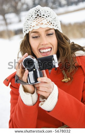 Smiling Caucasian young adult female in winter clothing pointing video camera at viewer.