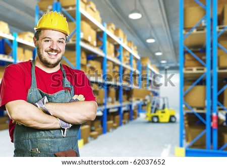 smiling caucasian young manual worker in warehouse - stock photo