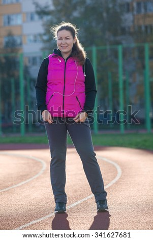 Smiling Caucasian young woman full length portrait, standing at the stadium in sportive clothes  - stock photo