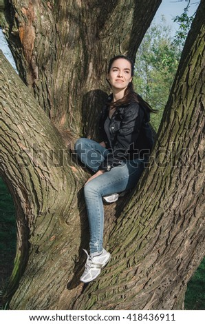 Smiling caucasian young woman in black jacket, blue jeans, white sneakers sitting on a tree trunk in the forest. Brunette female walking outdoors near park tree in morning sunlight. Summer nature. - stock photo