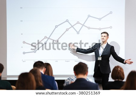 Smiling charismatic speaker giving public presentation in conference hall - stock photo