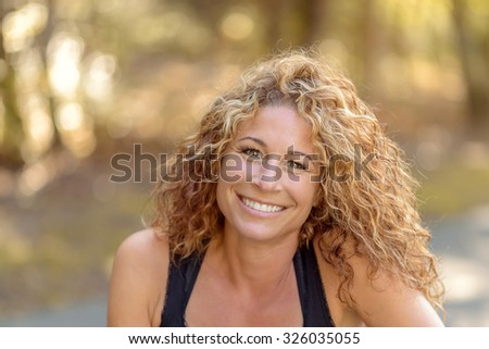 Smiling charismatic young woman with gorgeous curly long blond hair wearing a sleeveless summer top posing on a rural road giving the camera a warm friendly smile - stock photo
