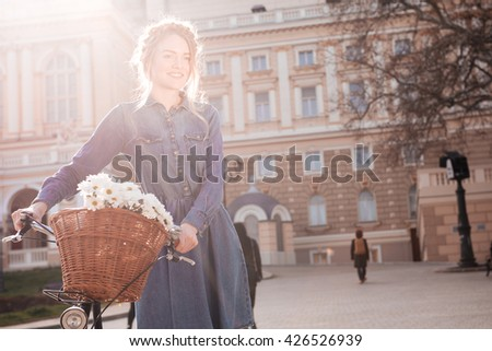 Smiling charming young woman standing with bike in the city - stock photo