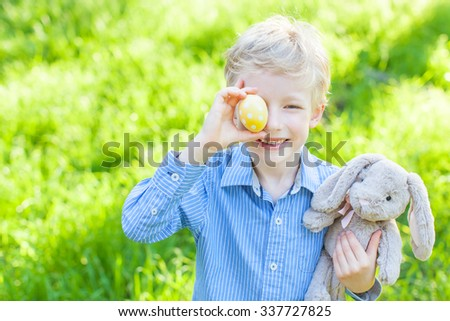 smiling cheerful boy holding colorful easter egg and bunny in the park enjoying spring time - stock photo