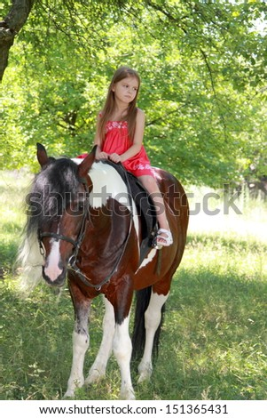 Smiling cheerful child riding a horse at a horse farm - stock photo