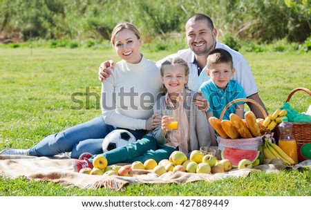 Smiling cheerful family of four having a picnic outdoors in a sunny weather - stock photo