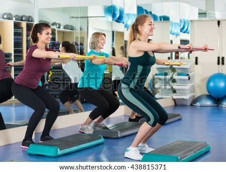 Smiling cheerful females working out on aerobic step platform in modern gym