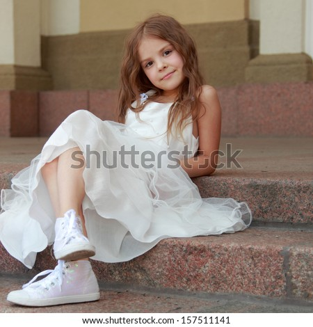 Smiling cheerful little girl in a beautiful white ball gown and sneakers sitting on the stairs to the outdoors