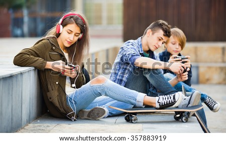 Smiling cheerful teens playing on smarthphones and listening to music - stock photo