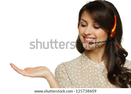 Smiling cheerful woman in headset holding empty copy space on her open palm, looking at palm, isolated on white background - stock photo
