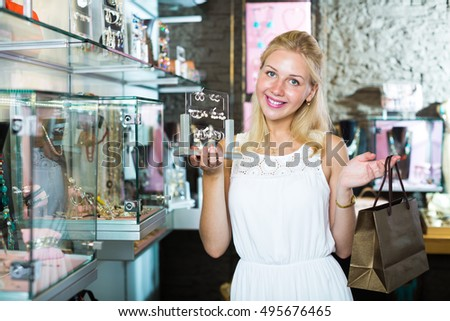 Smiling cheerful woman picking fashion earrings and gifts in jewellery boutique