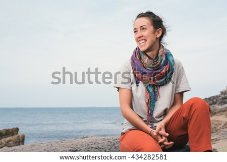 smiling cheerful young woman sitting on a rock by the sea. Summer Healthy happy lifestyle.