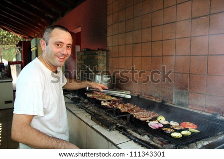 Smiling chef grilling meat in outdoor commercial kitchen. Chicken meat pieces being fried. Grilled chicken , pork and beef meat on the grill.Barbecue restaurant.  Delicious meat and on bbq grill.  - stock photo
