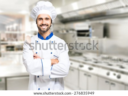Smiling chef in his kitchen - stock photo