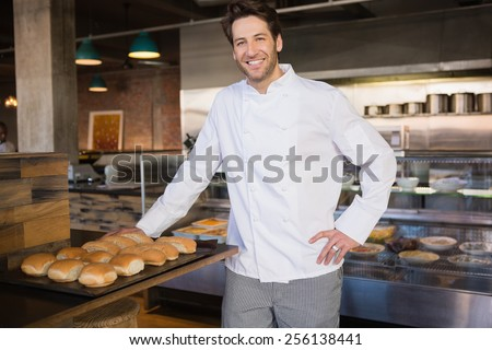 Smiling chef leaning on counter at the bakery - stock photo