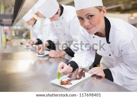 Smiling chef looking up from finishing dessert in the kitchen - stock photo