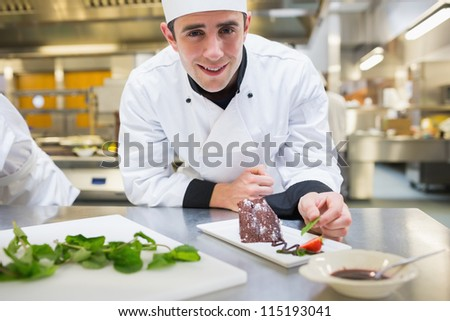 Smiling chef putting mint with his dessert in the kitchen - stock photo