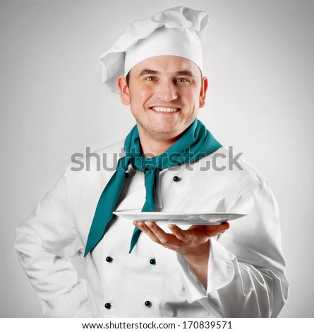 Smiling chef showing empty plate - stock photo