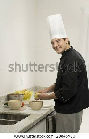 Smiling chef standing in kitchen peeling potatoes. Vertically framed photo. - stock photo