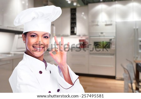 Smiling chef woman in a modern kitchen - stock photo