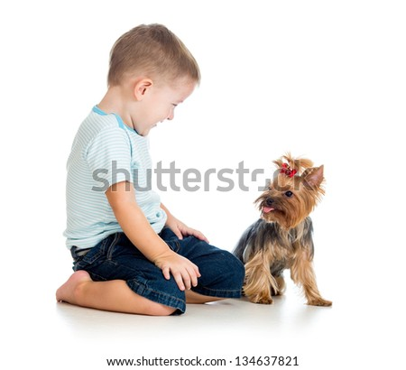 smiling child boy playing with a puppy dog isolated on white