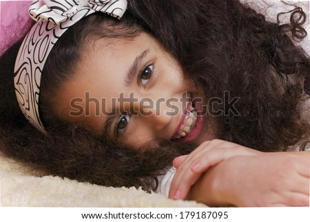 Smiling child brunette  swarthy girl lying in the bed - stock photo