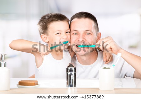 smiling child brushes his teeth with dad in the bathroom - stock photo