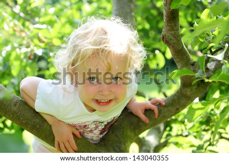 Smiling child climbing a tree in the garden - stock photo