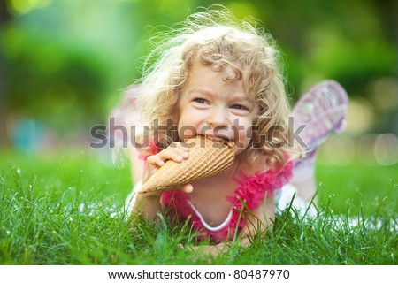 Smiling child eating ice-cream in summer park - stock photo