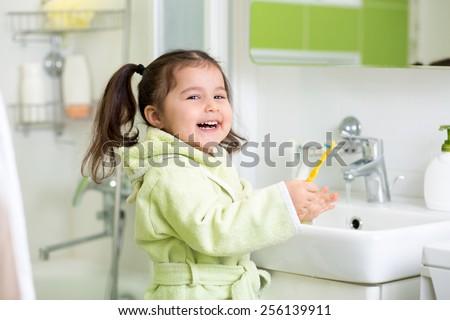 Smiling child girl brushing teeth in bath - stock photo
