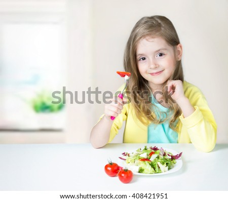 Smiling child girl happy  face sitting indoors at table eating vegetable fruit salad.Healthy kid's nutrition background empty copy space. - stock photo