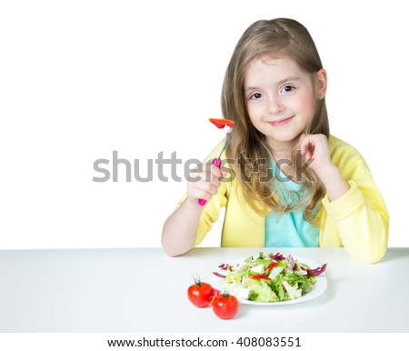 Smiling child girl happy face sitting indoors at table eating vegetable fruit salad isolated on white.Healthy kid's nutrition background empty copy space. - stock photo
