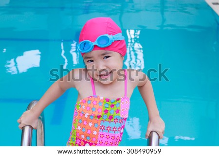 Smiling child girl swim in a blue pool - stock photo