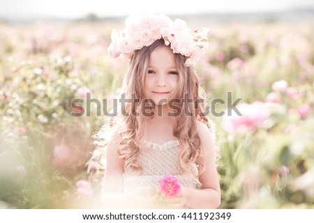 Smiling child girl 4-5 year old holding rose flower in meadow outdoors. Looking at camera. Childhood.  - stock photo