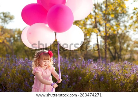Smiling child girl 3-4 year old with pink balloons outdoors. Birthday party. Playful. Childhood. Little princess.  - stock photo