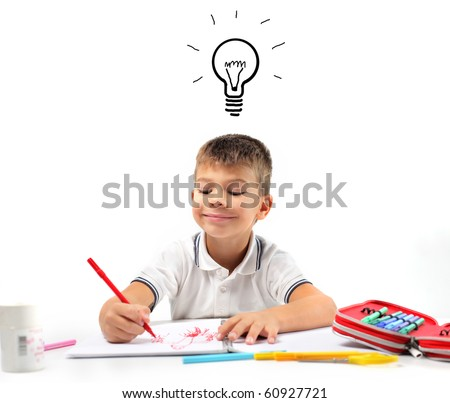 Smiling child having an idea while drawing - stock photo
