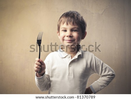 Smiling child holding a fork - stock photo
