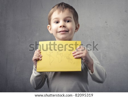Smiling child holding a paper sheet with the Earth on it - stock photo